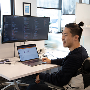 An AI2 employee smiling, sitting in front of his laptop.