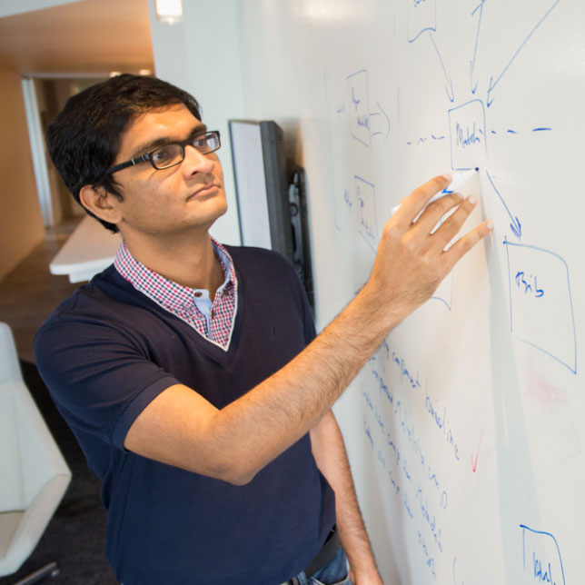 A researcher writing on a whiteboard