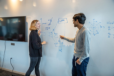 Two AI2 employees collaborating in front of a whiteboard.